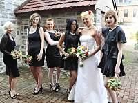 Black bridesmaid dresses with colorful bouquets.