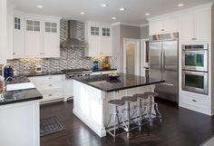 Traditional u shaped white cabinet kitchen with black countertops island and mosaic backsplash