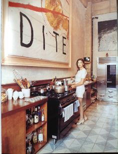 Olatz Shnabel in her kitchen  love the long shape, wood counters with white walls and giant piece of art on the wall.
