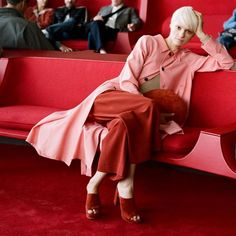 Flowy bubblegum pink trench coat, draped over a camel sweater and dark red cropped culottes, crimson suede slide heeled mules, and a red leather zip-top half-moon clutch, all by Mansur Gavriel.