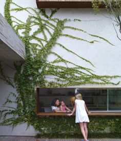 From the garden deck, Sophia Cóser talks to sister Helena and mother Piti through a wide, low-slung window typical of architect Marcio Kogan.  Photo by Cristóbal Palma.