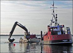 Bogø Havn. AVANCE graver ud til udvidelse af lystbådehavnen i 2012. Den eksisterende mole blev flyttet 50 m mod vest, og efter uddybning blev der rammet pæle ned på den anden side af den eksisterende bro, hvilket gav 30 nye bådpladser. Bogø Tidende, 25. januar 2012. Foto: Jørgen Stæhr