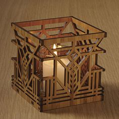 """The intricate, laser-cut design of this votive holder is adapted from stylized tulip windows of the Lake Geneva Hotel (Lake Geneva, Wisconsin, 1911). Made of sustainable Bamboo, includes a glass votive holder and a flicker LED battery operated tea light. 3-3/4"""" square.  Price:   $32.00 Qty.  1"""