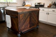 A custom kitchen island made from vintage wood, plumbing pipes and industrial casters contributes style and utility and is the perfect fit in this rustic industrial style kitchen, as seen on HGTV's Fixer Upper.
