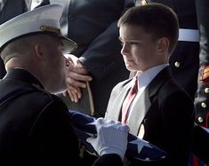 Eight-year-old Christian Golczynski accepts the flag for his father, Marine Staff Sgt. Marc Golczynski, during a memorial service. Marc Golczynski was shot on patrol during his second tour in Iraq (which he had volunteered for) just a few weeks before he was due to return home.