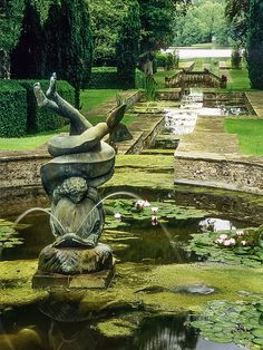 Dolphin and Putti Fountain, Buscot Park Gardens, Oxfordshire, UK:This photo shows part of the 'Alhambra – like' water feature designed by Harold Peto for this garden. It was initially laid out in 1904 with a central canal linking the house to an 18th century lake. This feature has a distinct Italianate feel – not surprising as Peto was a respected landscape architect who specialised in Italianate garden design. The photo shows the bronze 'dolphin and putti' in the foreground.
