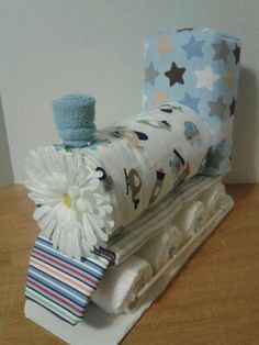 This cute train diaper cake ($40) is just chugging along! Covered with receiving blankets and using a wash cloth to release steam, it looks easy to re-create!