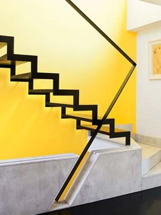 A floating staircase leading up from the ground floor creates a dynamic abstract shape against the bold yellow stairwell.