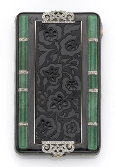 An art deco enamel, aventurine quartz, diamond, platinum and eighteen karat gold compact, France  designed with a central carved floral pattern, bordered by rows of aventurine quartz, accented by rose-cut diamonds set in platinum, opening to reveal powder and blush wells and a beveled edge mirror; signed SAM, reference #1295, imported to England 1927-1928, with pouch. dimensions: measuring approximately 3 3/16 x 1 9/16 x 1/2in. (minor loss to enamel)