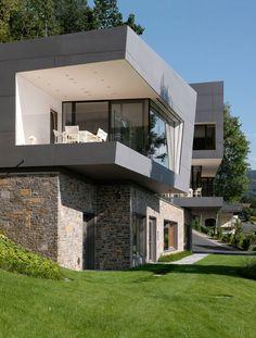 Rustikaler Sockel, moderner Überbau Mit interessanten Linien Haus am See mit Fassade aus fibreC Glasfaserbeton