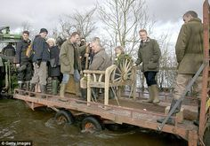 Shocking: Prince Charles perches on a 'throne' atop a tractor trailer during his first visit to Muchelney in February