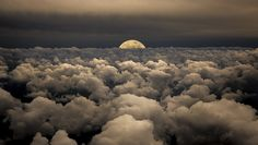 Fabulous composite photography - moon emerging through the clouds in the sky. Photography by Victor Caroli