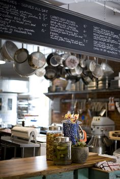 Open kitchen and table top displays at the George .like the pickles on the bar and the chalk board on top Parish Foods & Goods / (*The chalkboard strip over top of shelves in shop) Cafe Bar, Cafe Restaurant, Restaurant Design, Coffee Shop, Commercial Kitchen, Commercial Design, Commercial Interiors, Buffet, Food Places