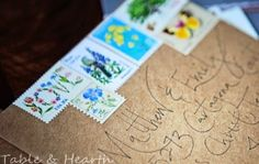 Rustic wedding invitation envelopes featuring hand-lettered calligraphy and vintage botanical stamps on Kraft paper