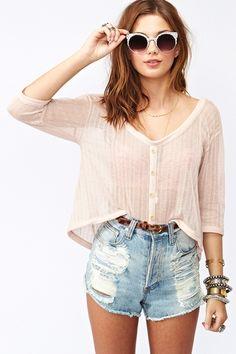 Creme long sleeved crop top brown belt jean high-waisted shorts.