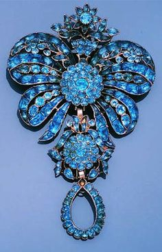 A blue paste brooch/pendant, 3rd quarter of the 18th century. Designed as a bow-knot with stylised floral accents and giardinetto surmount, suspending a detachable floral and foliate pendant, terminating in a further detachable pear-shaped swing drop, set throughout with variously shaped blue paste, all in closed-back settings, two paste and centrepiece of pear-shaped swing drop deficient, later brooch fitting, length 10.0cm., cased by W. Phillips, 492 & 494 Oxford Street, W.