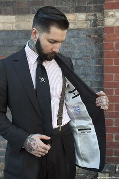 Now this is fit & flattering from cut to lining the suspenders are an unexpected but very nice touch the silver tie clip adds  A note of artistry  The blend of bad boy tats and bespoke gentleman are almost erotic