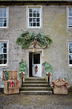 At her restored farmhouse in Cumbria Annabel Lewis, owner of specialist haberdasher's V V Rouleaux, has festooned her front door with pine boughs and bows, which lead down to two giant log baskets hung with ribbon.