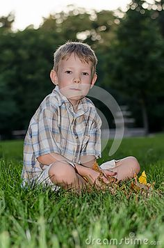Photo about Contemplative boy - child model sitting on the grass. Image of nature, checkered, modest - 58675732