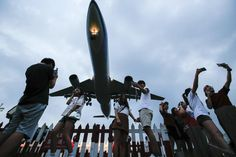 Un grupo de turistas se fotografía  bajo un avión militar C-130 durante su aterrizaje en Taipéi (Taiwan).