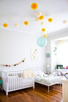 Ceiling lights are a great opportunity to make a visual impact on a room no matter the size and are also great for continuing the decor theme. Even though two kids inhabit the room, the pretty pom pom garlands make the whole space feel like a party