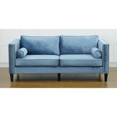 The soft blue velvet Cooper sofa brings comfort and style to any living area. This one of a kind sofa features a modern design with studded detail for a modern take on classic comfort.
