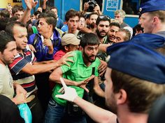 Migrants protest during the evacuation of the railway station by local police in Budapest. The main international railway station ordered an evacuation as hundreds of migrants tried to board trains to Austria and Germany, an AFP reporter at the scene said.  Attila Kisbenedek, AFP/Getty Images