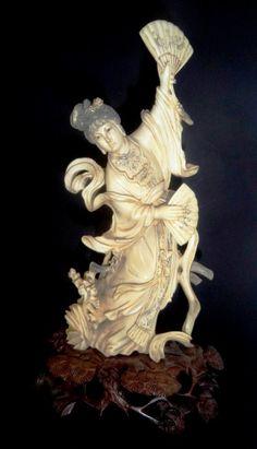 """Linda escultura em marfim representando figura feminina """"Dança com leque"""", apoiada sobre base em madeira ricamente entalhada. Altura com base 25 cm; sem base 22 cm. China, séc. XIX."""