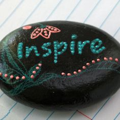 A small rock to remind you of a strength, goal or a motto. Inscribed with the word Inspire, with a base coat of black and accented with teal and
