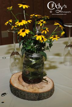 These table decorations are from a wedding I photographed...  mason jar on thin log with daisies, very nice, easie and inexpensive for a county outdoor themed wedding... personalize your wedding to the things you like. From Cindy's Photography in Ohio