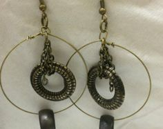 Hoop in green metal with chain in middle holding another hoop, and one more smaller hoop on bottom