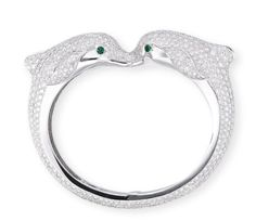 A DIAMOND AND EMERALD 'DOLPHIN' BANGLE, BY CARTIER. The hinged bangle designed as two pavé-set diamond dolphins enhanced by circular-cut emerald eyes, mounted in 18k white gold, inner diameter 6.3 cm, in red leather Cartier case. Signed Cartier, No. 744880.