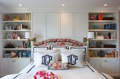 A multicolored floral upholstered headboard softens all the white crispness happening in this traditional bedroom. The deep built-in shelves and storage cabinets on either side of the bed are a brilliant space-saving move.