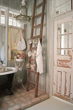 love how the tub is raised up on a brick floor, love the walls, love the light, the ladder, the chippy door...OH, just give me this bathroom!