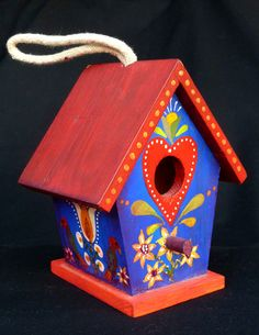 "Twin Swans Birdhouse Hand Painted by Alan Krug of ""Krug's Studio"" Etsy shop. The rich blue sides with cheerful red roof bring a bit of sunshine each and every day in a kitchen, garden room or any space that could use a spot of color for your home decor! The attached cord makes if very easy to hang. Using a Pennsylvannia Dutch motif of a double white swans, it has rose, pink and red hearts. It has been sealed with several coats of Varathane.  ~  bird house folk art garden art"