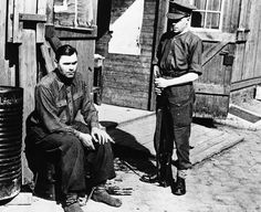 """Manacled following his arrest is Joseph Kramer, commandant of the Bergen-Belsen concentration camp in Belsen, photographed on April 28, 1945. After standing trial, Kramer, """"The Beast of Belsen"""", was convicted and executed in December of 1945."""