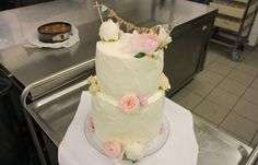 """white wedding cake with different real flowers. the banner says """"nygift"""" (just married)"""