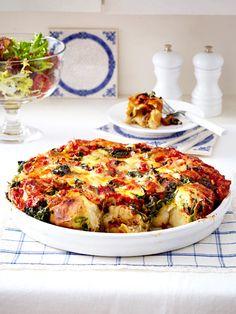 Statt auf den Frühstückstisch kommen die Sonntagsbrötchen hier als Pizzaboden zusammen mit Spinat, Käse und Tomaten in die Auflaufform.