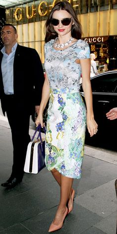 Miranda Kerr arrived at Sydney's David Jones store in a colorful print dress that she styled with retro shades, a statement necklace, leather Prada tote and pink pumps.
