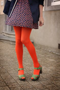 Orange tights, green platform sandals, polka dot dress and navy coat; vintage inspired mix.