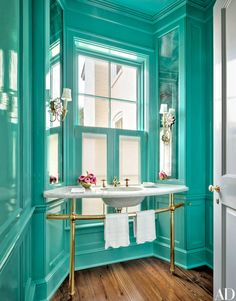 The powder room's walls and ceiling are painted in a high-gloss Sherwin-Williams turquoise. The washstand has brass sink fittings.
