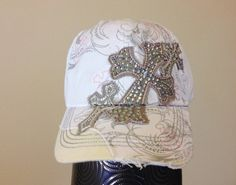 This distressed white baseball cap features a light grey screen printed pattern across the front and bill of the hat. There are small cross outlines embroidered all over the front and bill of the hat with pink thread and the front left corner of the hat is 'torn' back to reveal beige fabric for a fun asymmetrical look. Also featured on the hat are three grey crosses, with a pink contrast stitching outline, embellished with white rhinestones.  - Six-panel construction. - Embroidered design.