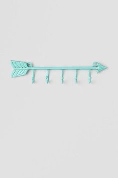 """The Blue Arrow Hook Wall Decor is perfect for hanging jewelry, keys, scarves, and more! Hang anywhere in your apartment, home, or office for a unique look!<br /> <br /> - 12"""" length<br /> - Five 2"""" hooks<br /> - Materials: metal<br /> - Features holes for nails (to hang)<br /> - Imported"""