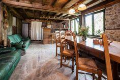 """Трапезарията, наричана още """"пивницата"""" на втората къща. Била е нещо като навес - три стени без таван и прозорци, а къщата е започвала от дървената стена вляво. Отварят прозорец, изграждат таван. Барплотът отделя кухненския кът от помещението. Тук родопски са само миндерите и белият китеник."""