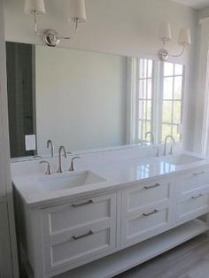 Creamy white bathroom cabinets painted Benjamin Moore White Dove, limestone tiles floor from Daltile (looks like wood), Thomas O'Brien Vendome Double Sconce and Cambria Torquay Quartz countertops (looks just like marble). by courtney