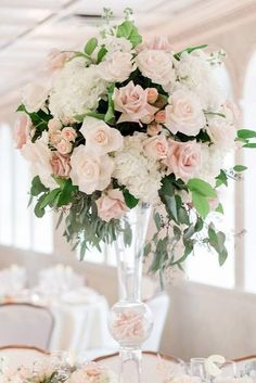 tall wedding centerpieces in a transparent glass vase white flowers and ruddy roses with greens amy rizzuto via instagram