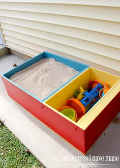 A colorful paint job and four bags of sand will turn a boring bookcase into a kid-friendly sandbox — complete with a compartment for sand toys.