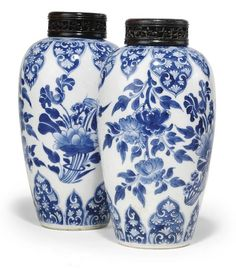 A PAIR OF CHINESE BLUE AND WHITE OVOID JARS AND WOOD COVERS  KANGXI (1662-1722)  Painted to the body with flowering lotus and hanging blossoms with leafy branches, the base edge and shoulder with foliate apron boarders, each with a later associated pierced wood fitted cover