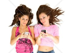 portrait of teenage girls holding cellphone. - Portrait of teenage girls typing a message over white background.