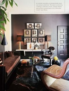 front door opens directly into the living area,  but the problem seems to have solved itself with this masculine take.  the art wall grouping, the suspended white shelf the only nod to  brightness, and the room looks wonderful, doesn't it?